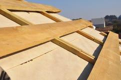Заволакивания мембраны крыши делая водостойким Обрамлять деревянной конструкции домашний с стропилинами крыши стоковое фото