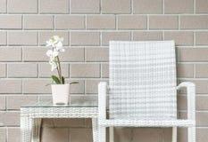 Завод крупного плана искусственный с белым цветком орхидеи на розовом цветочном горшке на деревянной таблице weave с деревянным с Стоковое Изображение RF