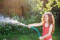 Завод маленькой девочки моча в саде на летнем дне Стоковое Изображение RF