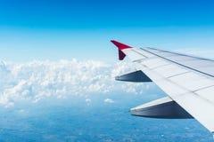 Заволоките окно самолета крыла воздушных судн взгляда голубого неба Стоковое Изображение