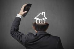Заволоките чертеж дома внутри головы бизнесмена в сером bac бетона Стоковые Фото
