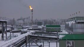 Завод под снегом в зиме с пламенем газа сток-видео