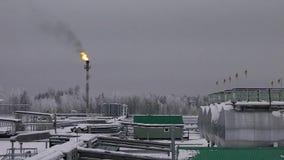 Завод под снегом в зиме с пламенем газа акции видеоматериалы