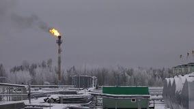 Завод под снегом в зиме с пламенем газа видеоматериал