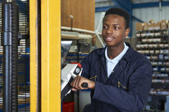 Заводской рабочий используя приведенный в действие аэродромный автопогрузчик для того чтобы нагрузить товары стоковое фото