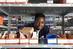 Заводской рабочий используя таблетку цифров в складе Стоковое Фото