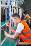 Заводской рабочий на производственной линии Стоковые Фотографии RF