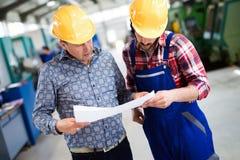 Заводской рабочий обсуждая данные с заведущей в фабрике металла Стоковые Фотографии RF