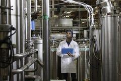 Заводской рабочий проверяя разливая по бутылкам фабрику Стоковое Изображение RF