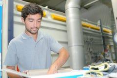 Заводской рабочий с рукой в коробке Стоковые Изображения