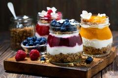 завтраки в опарниках с muesli, пюрем ягоды и сливк стоковое фото