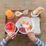 Завтрак американского завтрака очень вкусный для одного Женщина вручает яичко ножа для разрезания в сковороде над взглядом Стоковая Фотография RF