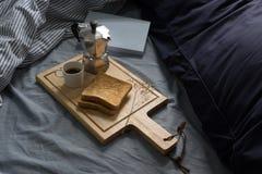 Завтрак в кровати, книге, эспрессо и здравице в утре стоковая фотография