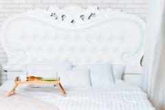 Завтрак в кровати, поднос кофе, круассаны и цветки honeymoon Королевская кровать в квартире просторной квартиры Рано утром на стоковое фото