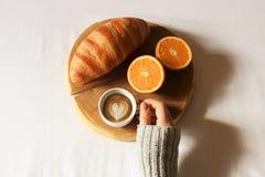 Завтрак в положении квартиры кровати Рука женщины держа чашку кофе, деревянный отрезок с свежим круассаном и апельсин в кровати В Стоковые Фото