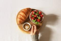 Завтрак в положении квартиры кровати Рука женщины держа чашку кофе, деревянный отрезок с свежим круассаном и клубнику в кровати В Стоковое Изображение RF