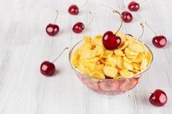 Завтрак лета с золотыми хлопьями мозоли, зрелыми вишнями на белой деревянной доске Декоративная граница с космосом экземпляра Стоковые Фото
