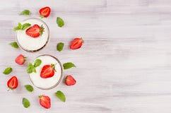 Завтрак лета с отрезанной клубникой, листьями чеканит на белой деревянной доске, взгляд сверху Декоративная граница с космосом эк Стоковая Фотография RF