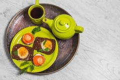 Завтрак - здравица с томатом обрабатываемого сыра, яичницами, яичницами, чашкой чаю чайника на серой предпосылке Стоковое Изображение