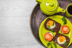 Завтрак - здравица с томатом обрабатываемого сыра, яичницами, яичницами, чашкой чаю чайника на серой предпосылке Стоковая Фотография RF