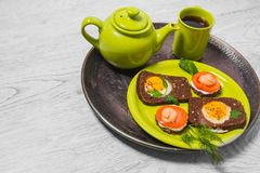 Завтрак - здравица с томатом обрабатываемого сыра, яичницами, яичницами, чашкой чаю чайника на серой предпосылке Стоковые Фотографии RF