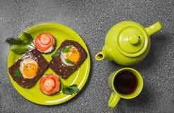 Завтрак - здравица с томатом, яичницами, яичницами, чайником и чашкой чаю обрабатываемого сыра на серой предпосылке Стоковые Изображения