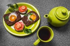 Завтрак - здравица с томатом, яичницами, яичницами, чайником и чашкой чаю обрабатываемого сыра на серой предпосылке Стоковое фото RF