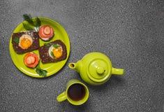 Завтрак - здравица с томатом, яичницами, яичницами, чайником и чашкой чаю обрабатываемого сыра на серой предпосылке Стоковое Изображение RF