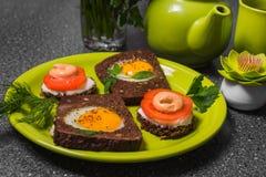 Завтрак - здравица с томатом, яичницами, яичницами, чайником и чашкой чаю обрабатываемого сыра на серой предпосылке Стоковое Изображение