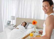 завтрак кровати принося счастливого человека Стоковые Изображения RF