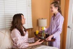 Завтрак мамы сервировки девочка-подростка в кровати Стоковое Фото