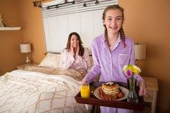 Завтрак мамы сервировки девочка-подростка в кровати Стоковые Фото