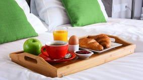 Завтрак на подносе в кровати в гостиничном номере стоковое изображение