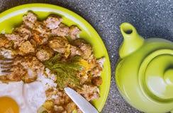 Завтрак - ростбиф и яичницы, чашка чаю на серой предпосылке Стоковое Фото