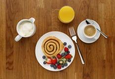 Завтрак свирли циннамона с плодоовощ, кофе и апельсиновым соком, стоковые фото