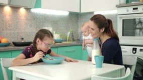 Завтрак семьи на утре Девушка есть хлопья мозоли с молоком на кухонном столе акции видеоматериалы