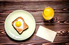 Завтрак состоит из яичек в форме сердца, здравицы и сока Рядом с завтраком примечание Стоковые Изображения RF
