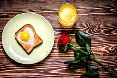 Завтрак состоит из яичек в форме сердца, здравицы и сока Стоковое Фото