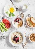 Завтрак таблицы - творог с югуртом и ягодами, овсяной кашей с медом и ягодами, яичницей, свежими овощами, домодельным g Стоковые Фото