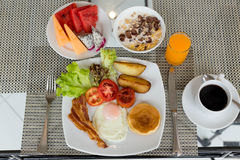 Завтрак установил на таблицу с блинчиками, беконом, яичками и кофе стоковые изображения