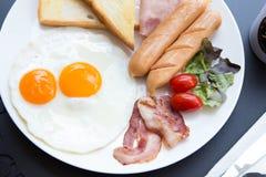 Завтрак установил на таблицу с горячими сосисками и беконом, яичками на черноте Стоковое фото RF