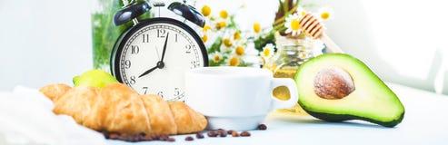 Завтрак утра, кофе в белом авокадое круассана чашки будя с будильником жизнерадостным, знамя здорового завтрака свежее Стоковое Изображение