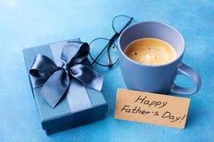 Завтрак утра с кофе, подарочной коробкой, поздравительной открыткой на счастливый день отцов и eyeglasses на голубой таблице Стоковые Фото
