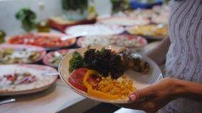 Завтрак шведский стол в ресторане гостиницы Девушка крупного плана кладет дальше плиту салаты видеоматериал