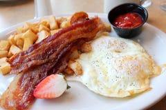 Завтрак яичек, бекона и картофельных оладьей на белой плите Стоковые Изображения RF