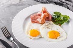 Завтрак, яичницы, бекон, ветчина, свежий салат на плите на серой поверхности таблицы Здоровая еда, взгляд сверху стоковые изображения rf