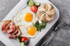 Завтрак, яичницы, плюшка, бекон, ветчина, свежий салат на плите на серой поверхности таблицы еда здоровая стоковое изображение rf