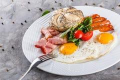 Завтрак, яичницы, плюшка, сосиска, бекон, ветчина, свежий салат на плите на серой поверхности таблицы еда здоровая стоковые фото