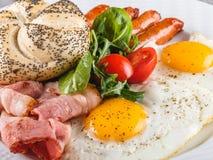 Завтрак, яичницы, плюшка, сосиска, бекон, ветчина, свежий салат на плите на серой поверхности таблицы еда здоровая стоковые изображения
