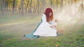 Загадочная сиротливая рыжеволосая девушка сидит на том основании, зеленая трава в лесе и принимает вне 2 сочных яблока сток-видео